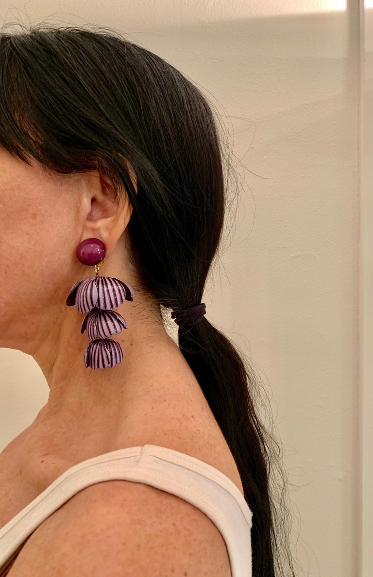 Light and easy to wear, these handmade artisanal contemporary clip-on earrings were made in Paris by Cilea. The lightweight statement earrings feature three rows of architectural enameline (enamel and resin composite) purple flower petals. The