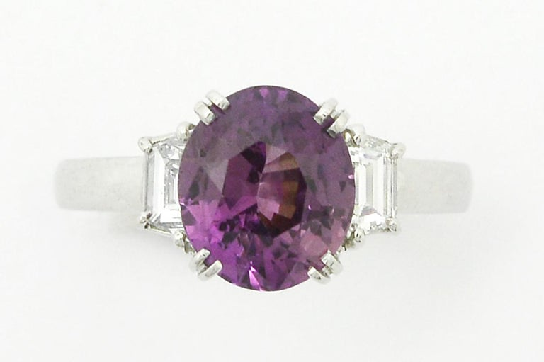 A passionately beautiful purple sapphire engagement ring in an elegant 3 stone setting. Taking center stage is a 3.23 carat captivating, brilliant and lively natural sapphire of a shimmering shade of pinkish lavender with a fabulous luster. The