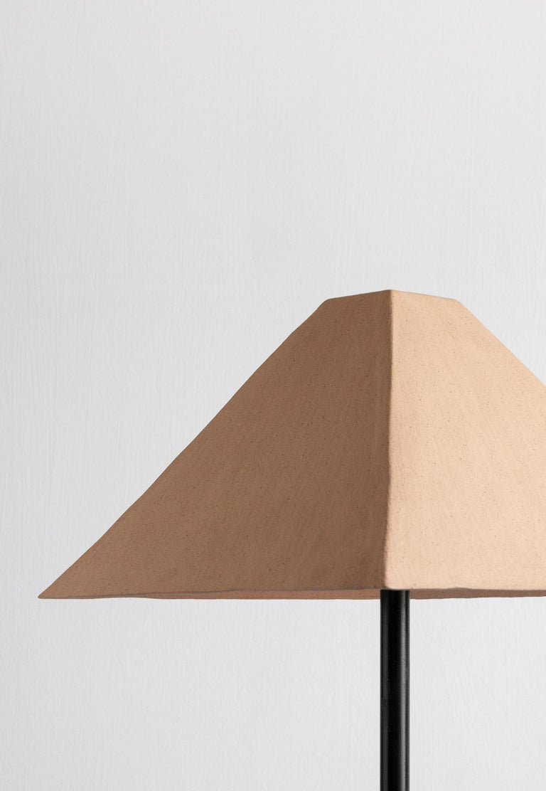 The elegant and clean lines of the Pyramid shade are handcrafted by the hands of skilled artisans using a slip-cast process. Available in a variety of finishes, this table lamp is perfect as a decorative and sculptural pieces just about