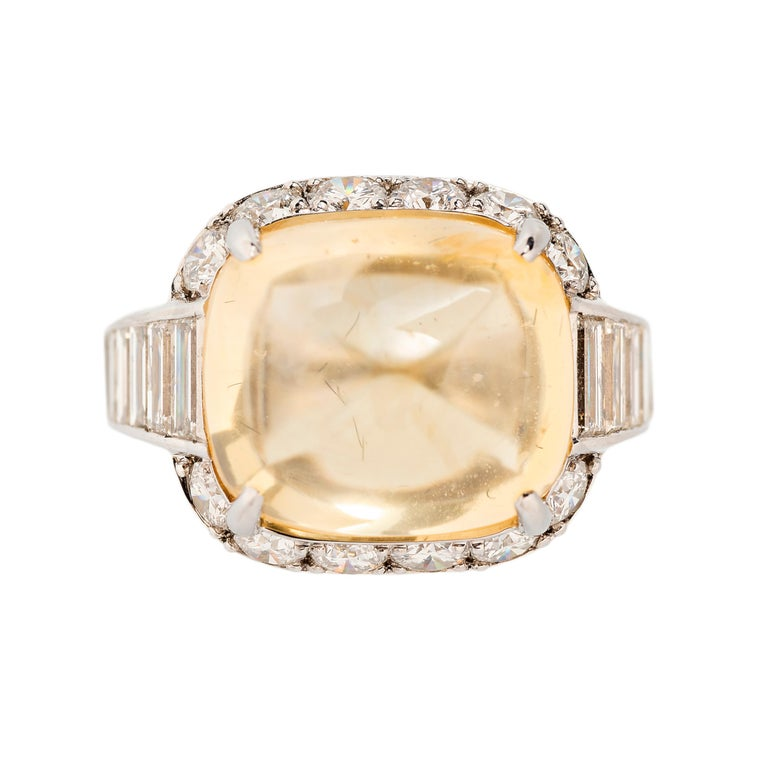 A classic Art Deco design highlights this radiant 13.66 carat no heat medium canary yellow cabochon sapphire. The center stone is surrounded by 6 full-cut pave-set diamond melee and each side of the shank is set with seven baguette diamonds.     -