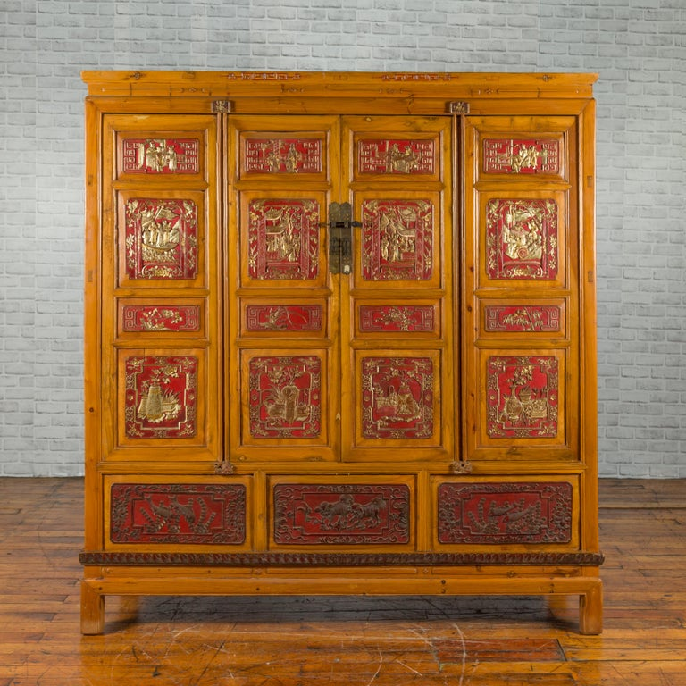 A large Qing dynasty Chinese hand carved, painted and gilded armoire from the 19th century, with 19 panels, four doors and three removable panels revealing a secret compartment. Created in China during the Qing dynasty, this large armoire draws our