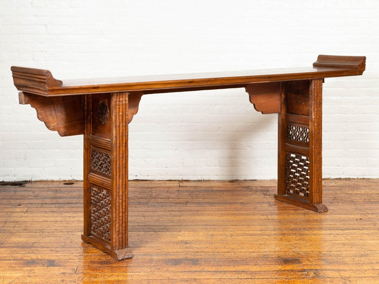 A Chinese Qing dynasty period altar console table from the early 20th century, with everted flanges, hand carved bamboo style design and fretwork motifs. Born in China during the Qing dynasty, this altar console table features a rectangular top,
