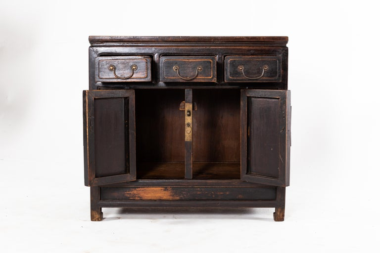 This cabinet is from Beijing, China and was made from walnut, circa 19th Century. The piece features 3 drawers, a pair of doors, its original lacquer, and a shelf for storage. Wear consistent with age and use.