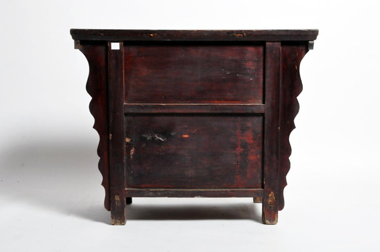This Qing dynasty butterfly cabinet is from Shandong, China and was made from elmwood and lacquer, circa 19th century. The piece features 2 drawers, a pair of doors, and its original patina. Wear consistent with age and use.