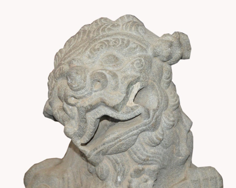 A Chinese Qing dynasty hand-carved stone foo dog temple sculpture from the late 17th century mounted on custom base. This foo dog sculpture features a lion sitting on his hind legs with his front left paw resting on a decorated rail while his right