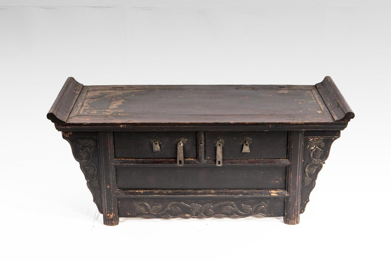 This handsome chest from Shandong, China is made of elm wood and dates to the middle-Qing dynasty. The piece features hand carved floral detail, its original patina, and two drawers. The piece has a beautifully aged patina; wear consistent with age