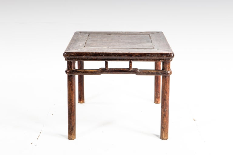 This small side table dates to the middle-Qing dynasty. The piece is made of elm wood and features humpback stretchers and a beautifully aged patina.