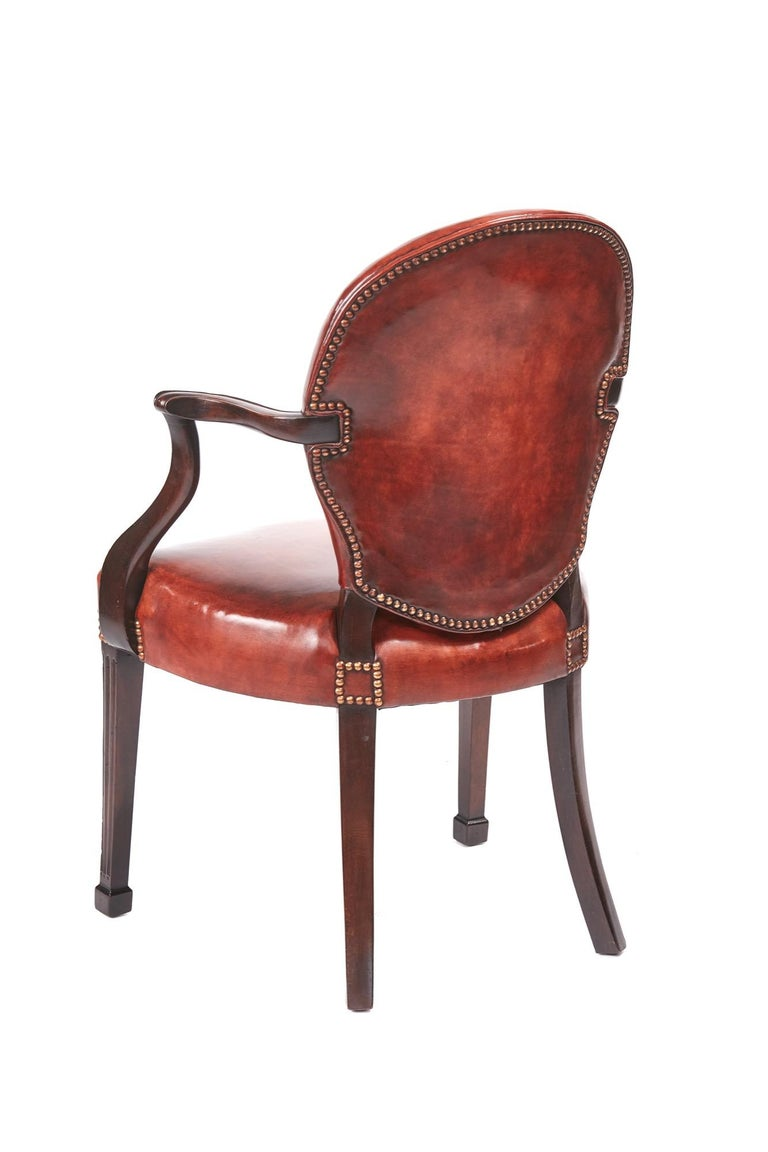 Quality antique mahogany desk chair, having a lovely chestnut brown leather back and seat, lovely shaped open arms, standing on square tapering reeded legs with block feet to the front outswept back legs Lovely color and condition. Measures: 23