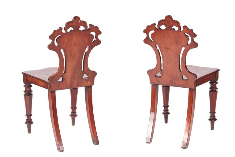 Quality pair of William IV mahogany hall chairs, with lovely carved solid mahogany shaped backs, mahogany seats, shaped turned legs to the front outswept back legs
