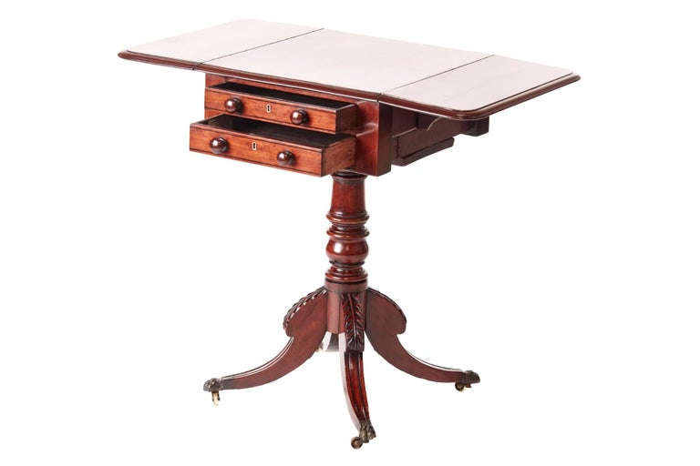 Quality Regency mahogany drop leaf lamp table, having a lovely quality mahogany top with two drop leaves, two drawers with original turned mahogany knobs, supported by a solid mahogany turned column, raised on four carved reeded sabred legs