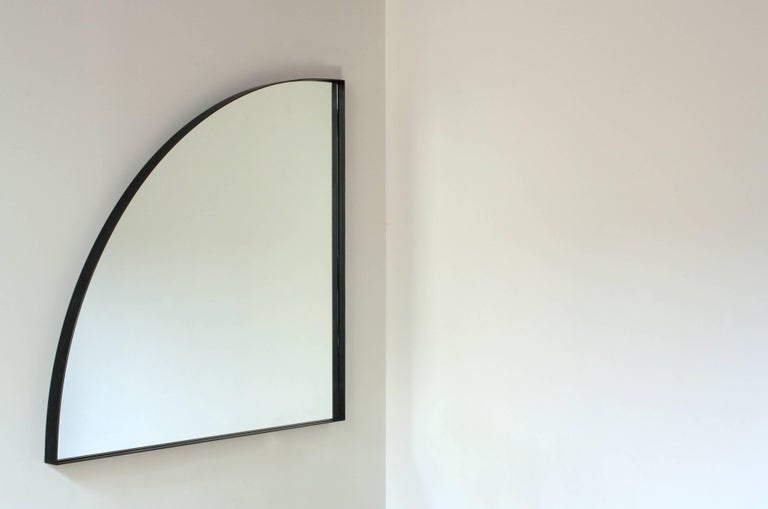 Handmade in Chicago by Laylo Studio, this customizable mirror features a clear, quarter-round mirror with polished edges centered inside a blackened steel frame. A gentle arc connects two points equidistant from the corner matched by the curved edge