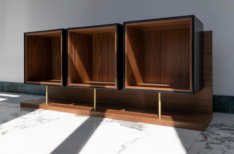 Quartet uses a single L-shaped support to bear the three cubic leather modules, forming the back and base sections, both of which reveal the longitudinally arranged long wood grain of Canaletto walnut, making this an object to display at the centre