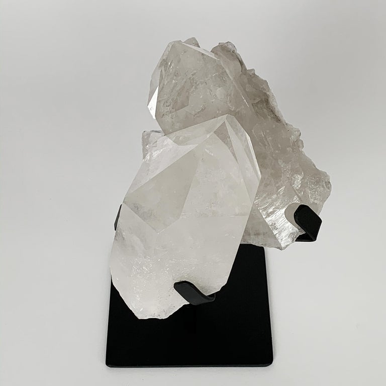 Large natural quartz crystal specimen mounted to a pronged painted black metal stand. Measures: 9