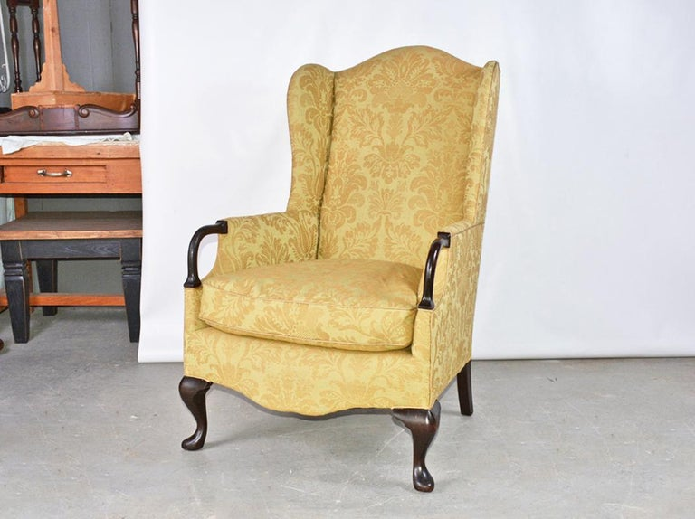 An elegant and well proportioned wing back arm chair with rounded wood arm handles making it easier to get in and out of the chair, terminating in Queen Ann style legs. Victorian.