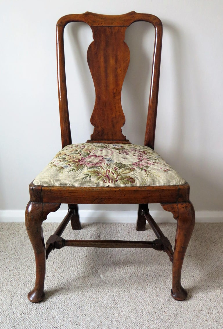 This is a classic English walnut chair from the Queen Anne period with a beautiful mellow color and dating to circa 1700-1710.