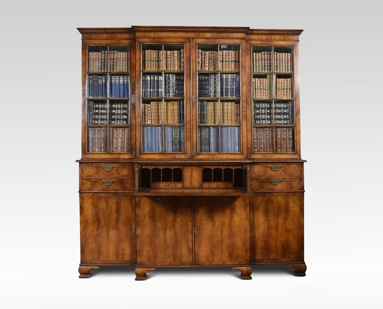 Queen Anne revival walnut four door bookcase, the projecting cornice above, four large glazed doors opening to reveal fixed shelved interior. To the base section fitted with a central secretaire drawer and original inset leather. Flanked by short