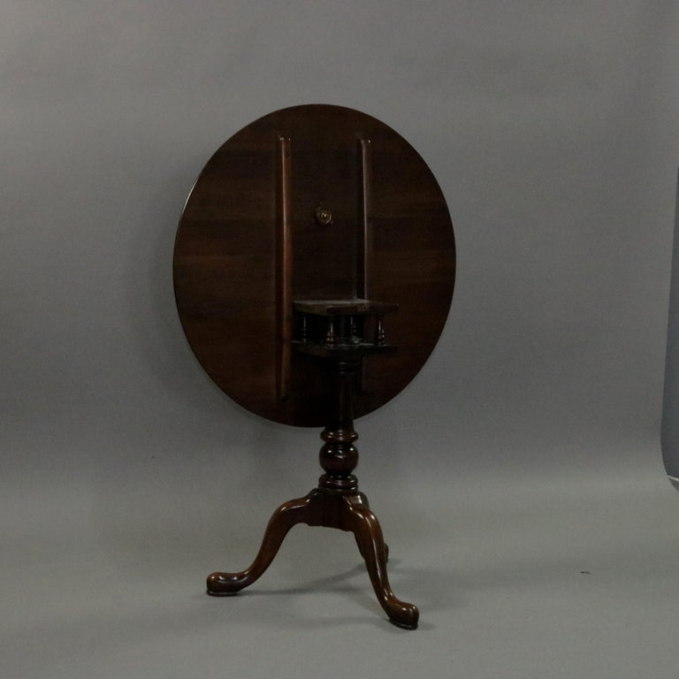 A Queen Anne style tilt-top side table features mahogany construction with round tilt-top having birdcage surmounting turned tripod base seated on cabriole legs with pad feet, 20th century.  ***DELIVERY NOTICE – Due to COVID-19 we are employing