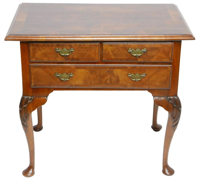 A Queen Anne walnut and burl walnut lowboy dressing table. The top with figured burl walnut with walnut cross banding above a pair of short drawers over a single long drawer, standing on legs carved with overlapping shell design ending in pad