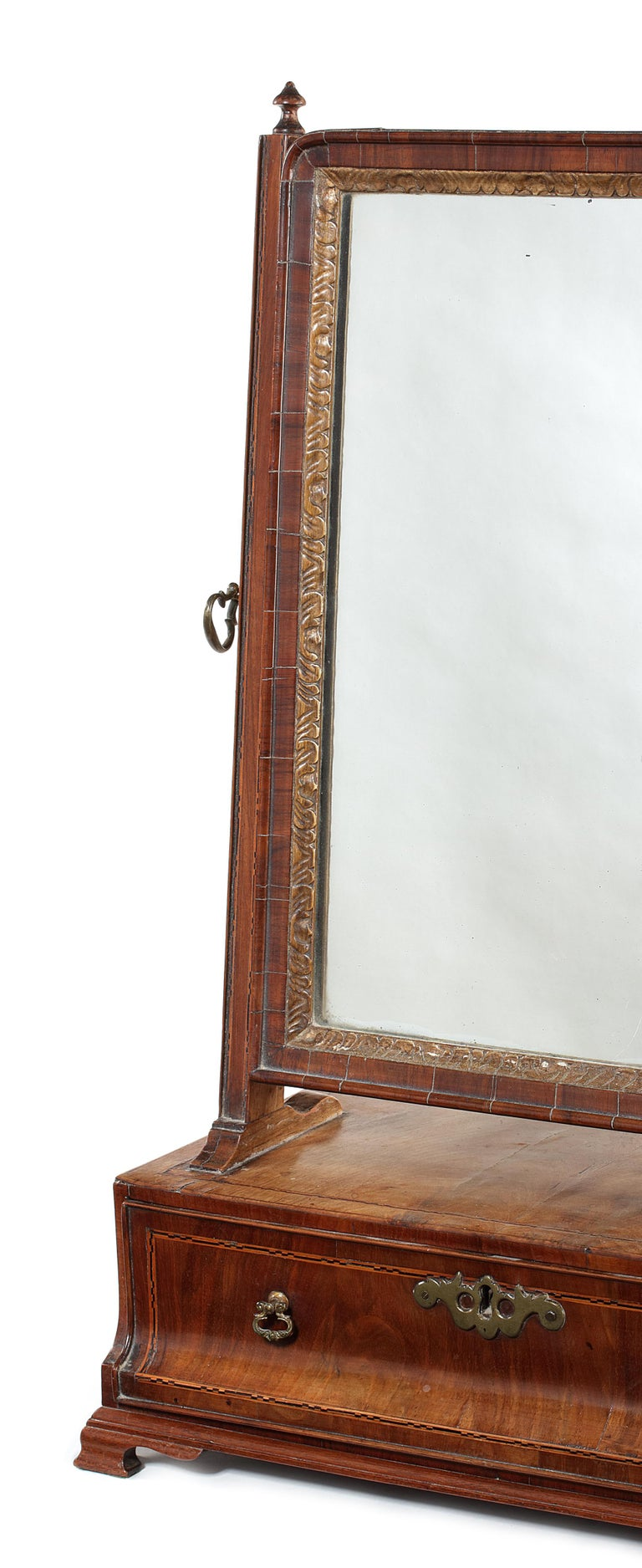 Queen Anne walnut and chequerbanded toilet mirror The replaced plate with a leaf carved slip and moulded swing frame, the rectangular base with concave drawer on later plinth and ogee bracket feet, 41cm wide, 22cm deep, 63cm high.