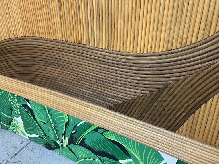 Queen size rattan bed headboard features full veneer of pencil reed rattan in a decorative pattern. In the style of Betty Cobonpue. Very good condition with only minor imperfections consistent with age.