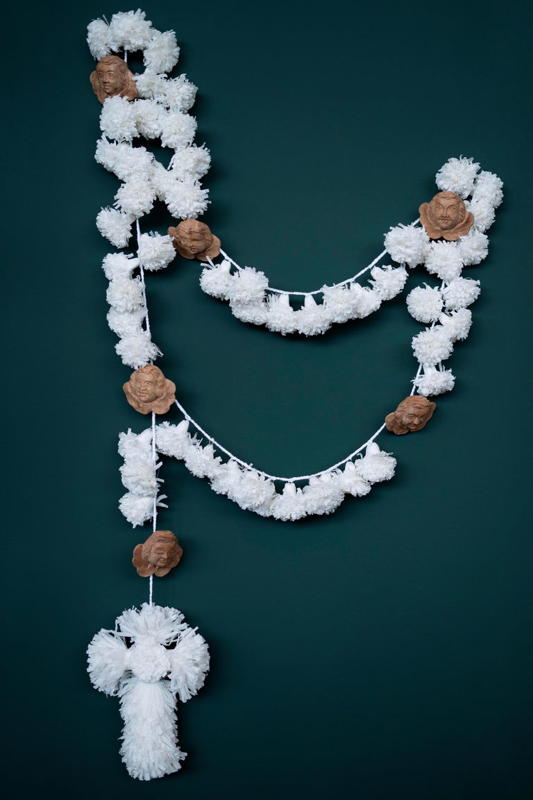 This Rosary is made with crepom paper pompons and cross, a work of D. Lilia Fonseca, and hand wood carving querubins, made by Rondinelly Santos, D. Lilia's nephew, and a sacred art sculptor. All this pieces are put together by D. Maria Conceição de