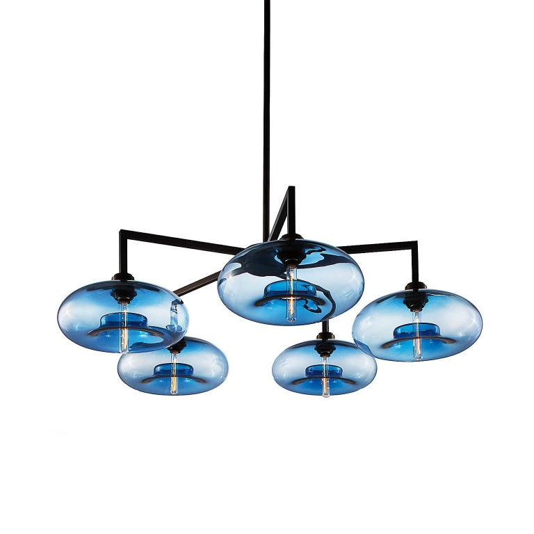 The refined frame of the Quill chandelier accentuates the handcrafted silhouettes suspended from its bold body. With several signature glass and metal finish options available, the wide range of configurations offered in this collection enables the