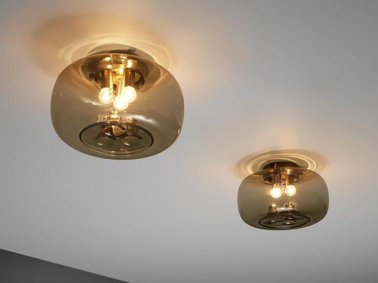 RAAK Amsterdam, ceiling light, smoked glass, brass, the Netherlands, 1970s  Inside an oval glass shade are hold three small lightbulbs on brass cylindrical mountings by RAAK Amsterdam. The lightbulbs have an equivalent form in the bottom of the
