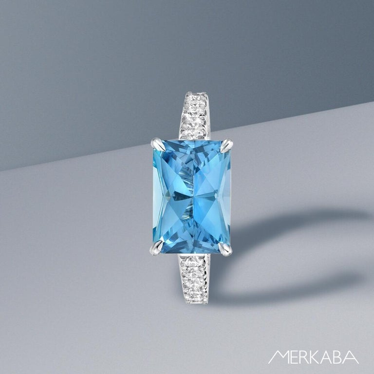 This unique, custom cut 2.59 carat Aquamarine, blends an emerald cut outline with a radiant cut, to maximize the brilliance of the gem. It is hand set horizontally in a striking 0.52 carat round brilliant diamond platinum cocktail ring, crafted
