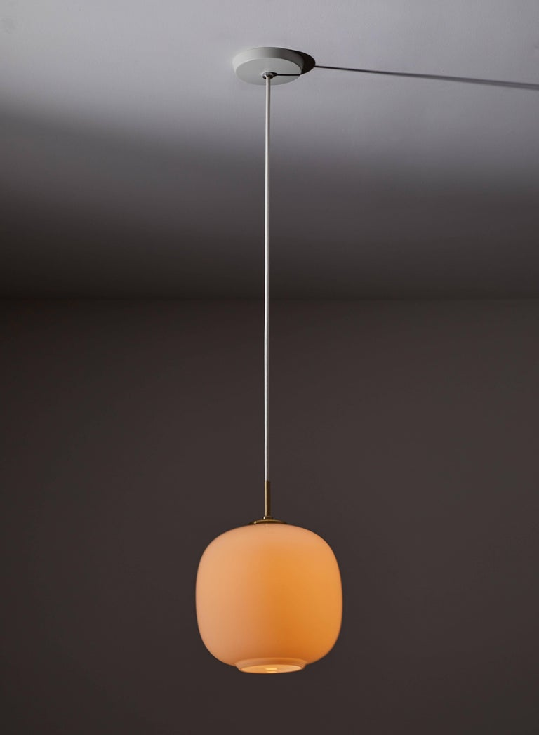 Small Radiohus VL45 pendant by Vilhelm Lauritzen for Louis Poulsen. Current production designed and manufactured in Denmark. Opaline glass and brass Hardware. Currently, the VL 45 Radiohus pendant Light is being reintroduced with the same original