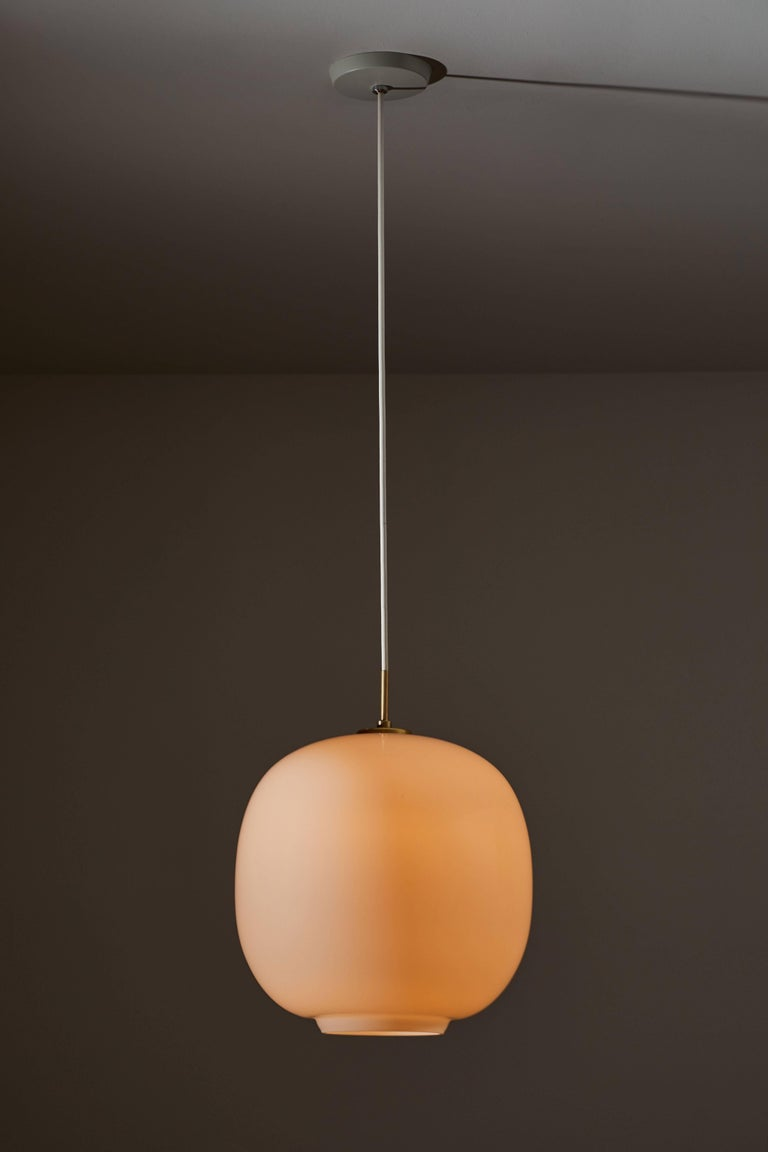 Large Radiohus VL45 Pendant by Vilhelm Lauritzen for Louis Poulsen. Current production designed and manufactured in Denmark. Opaline glass and brass Hardware. Currently, the VL 45 Radiohus Pendant Light is being reintroduced with the same original