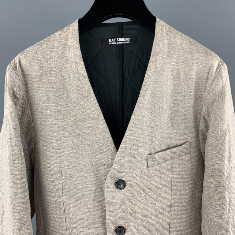 RAF SIMONS Spring Summer 2009 Collection sport coat jacket comes in a khaki beige quilted linen material with a collarless V neck, three button front, and simulated slit pockets. Altered to fit a slim silhouette and minor wear.   Good Pre-Owned