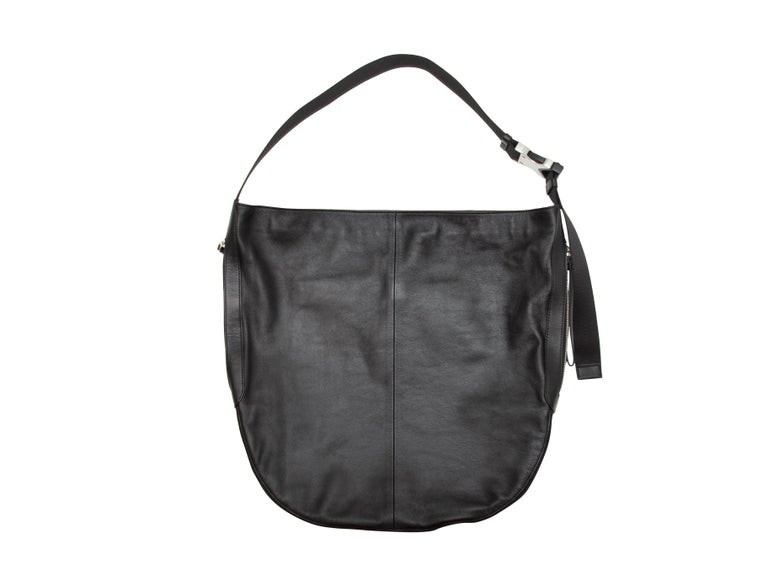 Product details: Black suede Riser Carryall bag by Rag & Bone. Canvas interior. Silver-tone hardware. Leather at back. Single strap. 17