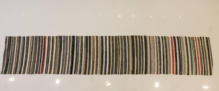 Hand-stitched fabric rag runner showing a succession of multicolor stripes, measuring 152