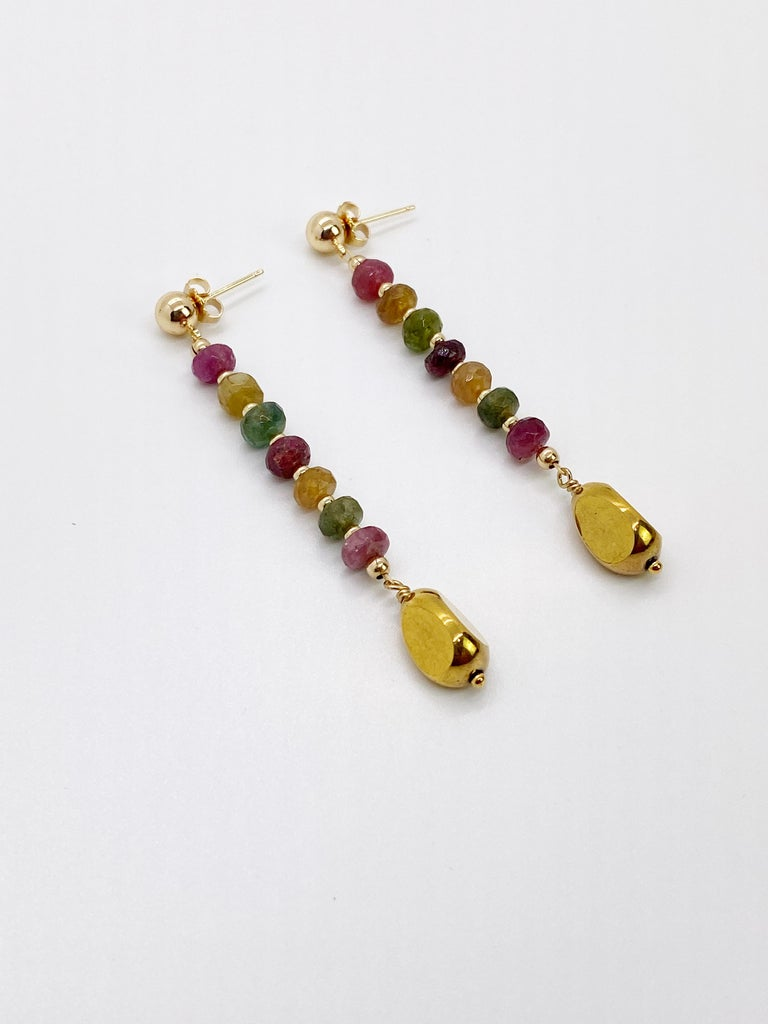 A large vintage German glass bead that is plated with 24K gold dangles on beautiful deep color 5-6mm faceted round tourmaline. They are finished with 14K gold-filled beads and ear studs. The earrings dangle and sways beautifully and freely. They are
