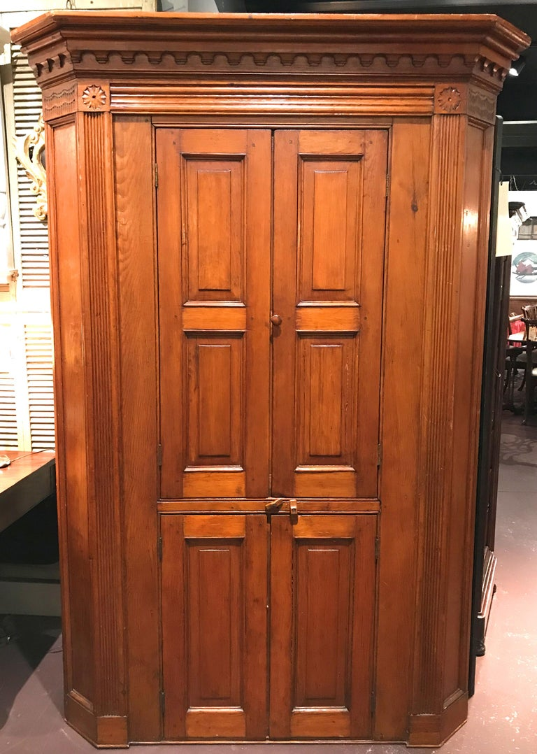 A fine raised panel cupboard featuring a molded and carved cornice with corner rosettes above fluted pilasters and flanking two pairs of raised paneled doors the upper opening to reveal two nicely shaped shelves with blue interior over the lower