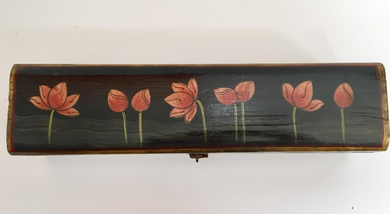 Hand painted Rajhastani decorative writing box. Hand painted wood in rectangular shape with hinged lid and decorated with floral designs on black.
