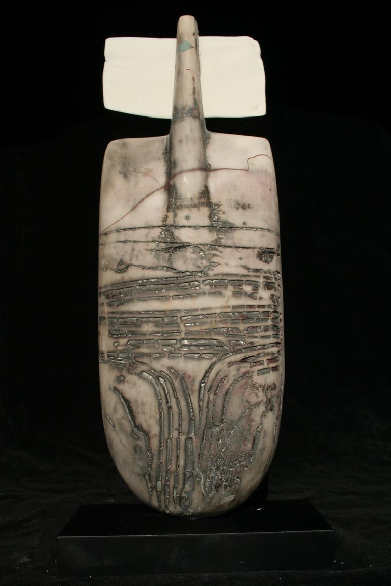 This obelisk shaped object is completely handmade, raku fired ceramic. The surface is textured with ridges and grooves which have a variegated patina due to a natural aging process the artist uses. The artist has adorned top of the sculpture with