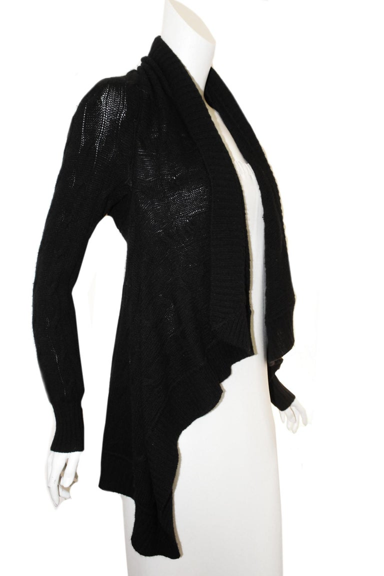 Ralph Lauren black cable knit cashmere shawl sweater is open at front with an asymmetrical collar.  This unlined sweater is shorter at front and just below the hip at  back.   This cozy soft shawl cardigan is in very good condition with minor pulls.