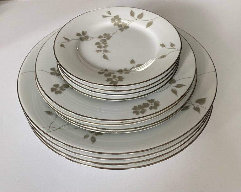 A set of four (4) dinnerware place settings in the Sophia pattern by Ralph Lauren Home. Signed, production period 2000-2002.  Features a delicate floral pattern in gray or green.  Includes 4 place settings. A total of 20 pieces. Each setting