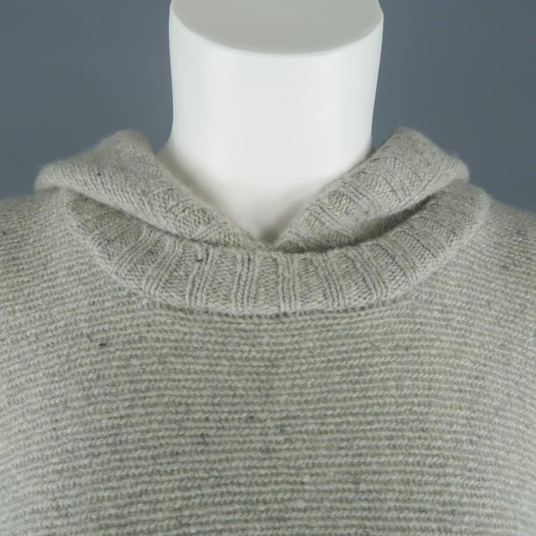 Ralph Lauren Black Label poncho comes in light speckled gray cashmere knit and features a round neck with hood, frontal hoodie pocket, and half closed sides.   Excellent Pre-Owned Condition. Marked: M/L   Measurements:   Width: 44 in. Length: 31 in.