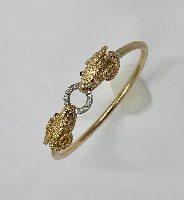 The stunning bangle bracelet is set with two Ram, Sheep, Aries heads.  The mouths of the Rams hold a Diamond circle and the eyes of the Rams are fine red Rubies.  The bracelet is a classic Greek Revival motif.  It is exquisite with beautiful three