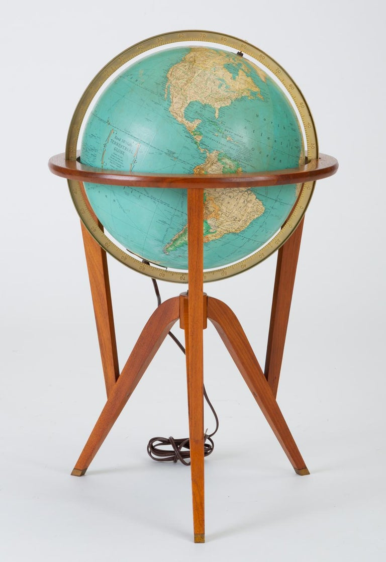 "An illuminating globe in a walnut stand designed by Edward Wormley (of Dunbar) for map company Rand McNally. Dubbed the ""Cosmopolitan,"" the globe has an X-base of four tapered walnut legs with brass feet, and a broad ring of walnut to support the"