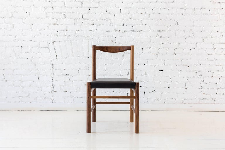 Shaker inspired walnut chair with comfortable contoured back rest. This chair's simplicity makes it versatile to work well in many different environments.  Available with a plain walnut seat pan or seat pan with a low profile black leather pad or