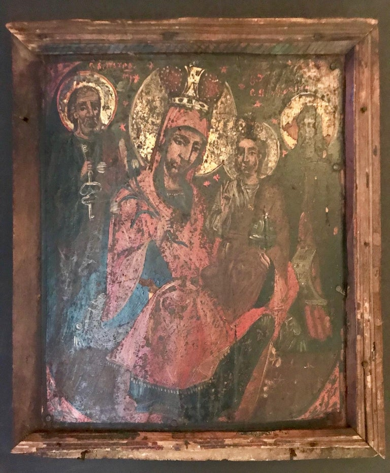This exceptional icon was created the late 1600s in Russia. Icons are considered to be gospel in paint. This one depicts four saints. It is painted with egg tempera on a wood panel, which has warped only slightly with age. Soot from burning candles