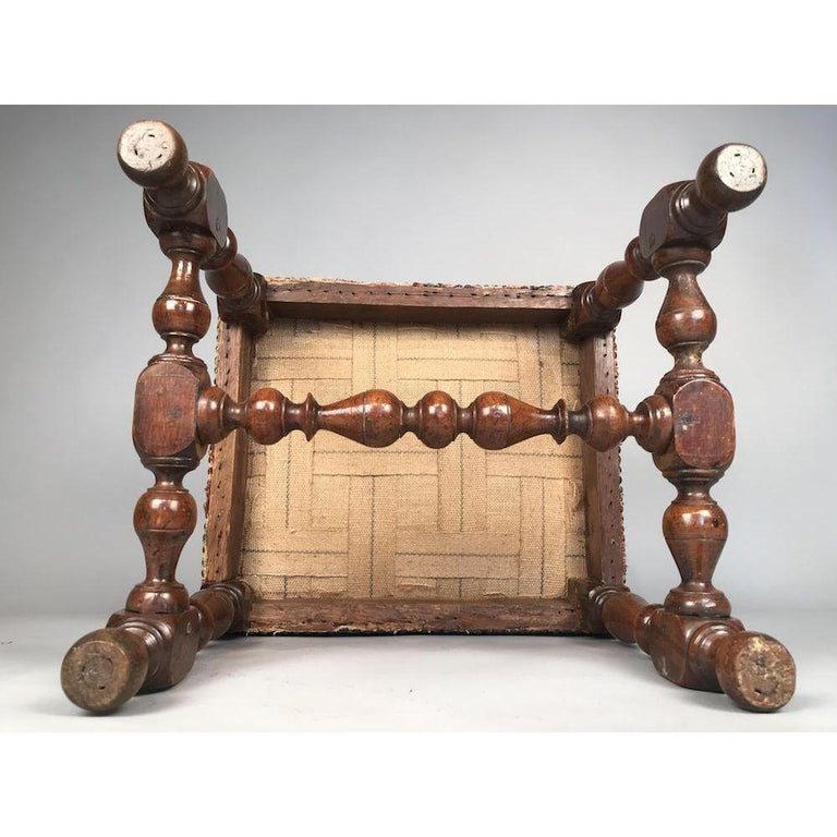 A rare late-17th century walnut stool of lovely color and surface patination, circa 1680. On bobbin-turned supports and stretchers. Upholstered in old needlework, and close-nailed. All in excellent original condition.  See Ralph Edwards CBE FSA 'The