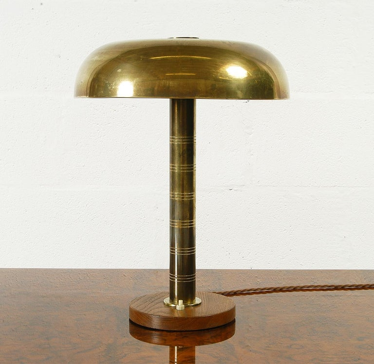 A really good example of Post War Swedish Modernism; this brass and wood table lamp was manufactured by Bohlmarks Belysning of Stockholm Sweden, and is very similar to pieces designed by both Harald Notini and Bertil Brisborg. The lamp is in as
