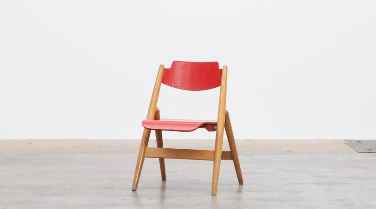 Kids folding chair, beech wood by Egon Eiermann, Germany, 1952.  The folding childrens' chair with red lacquered seat and backrest is designed by influential German designer Egon Eiermann.   His multiplicity of occupations also included