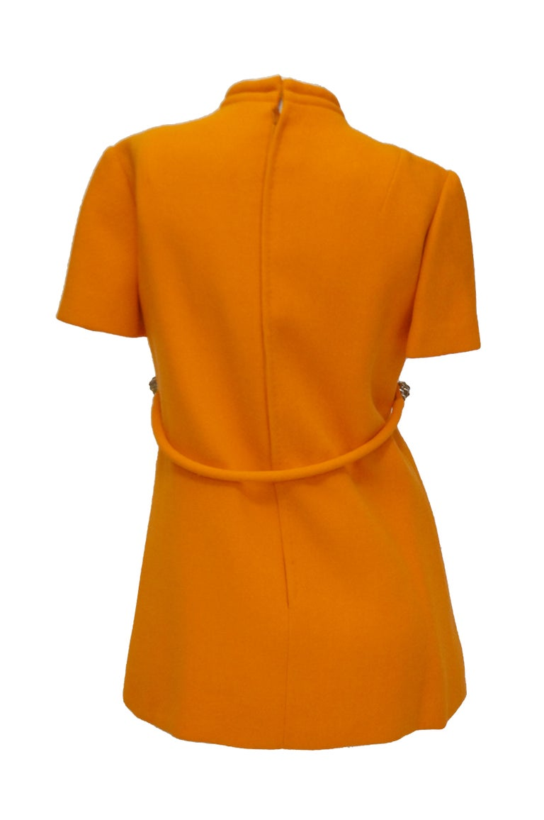 1960s Bill Blass Orange Mod Mini Dress with Nugget Belt Detail  Fantastic futuristic bright orange dress by Bill Blass! The dress is mini length, with short sleeves, a high faux turtle neckline large box pleating on the front. The bodice has an
