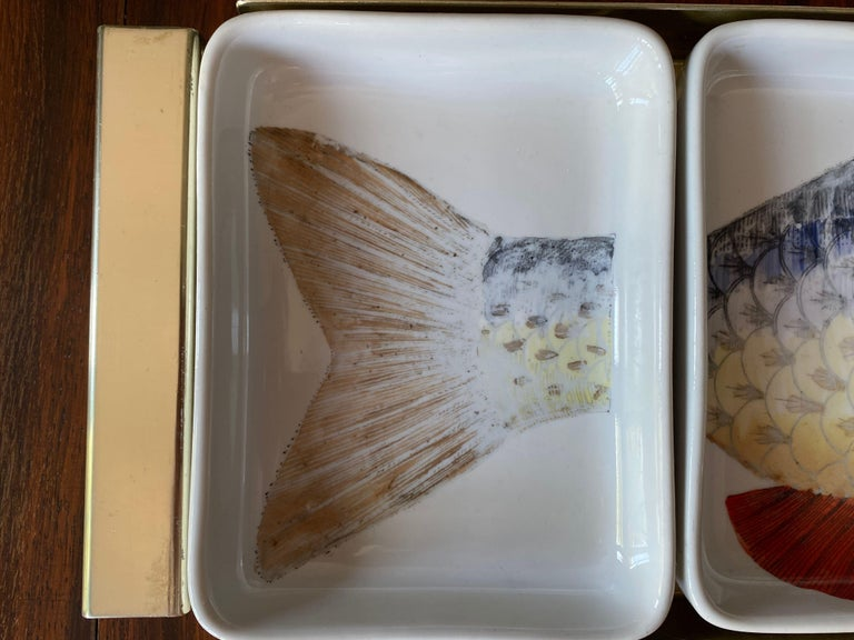 Appetizer tray consisting of four ceramic dishes  Gold metal tray  Printed section of fish on each dish  Fornasetti mark underneath  Slightly faded print  Reference: Fornasetti: The Complete Universe, Edited by Barnaba Fornasetti,