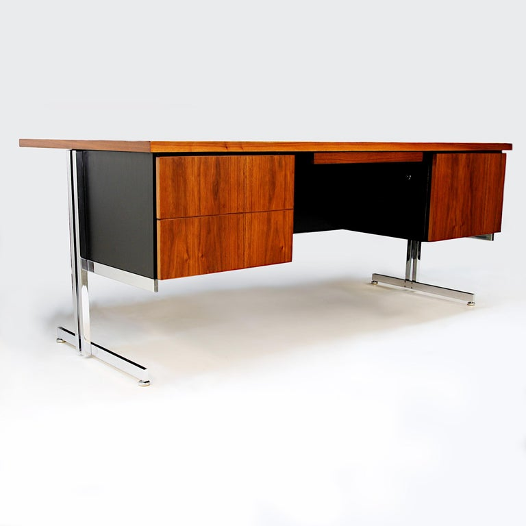 Rare executive desk designed by Hugh Acton for the Vecta Contract Co. Desk features matched-grain walnut cabinetry cantilevered over the Classic Acton chromed-steel base. With its wonderful, architecturally-inspired, Minimalist design, this would